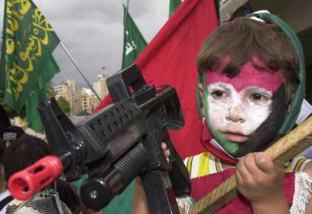 small Palestinian girl with toy rifle at anti-Israeli rally